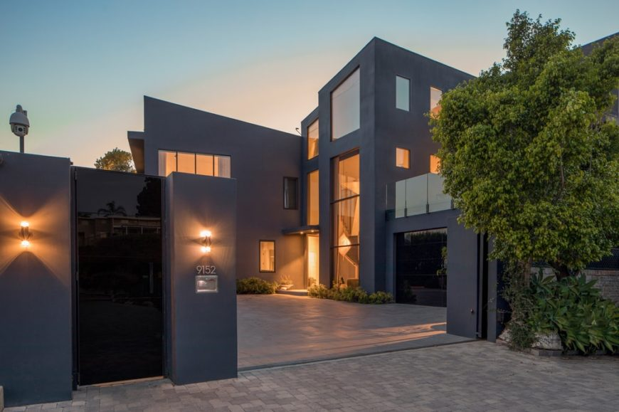 This is the front view of the house with gray exteriors complemented by the yellow lights and large glass elements. Image courtesy of Toptenrealestatedeals.com.