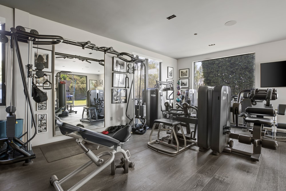 This is the home gym that is well-equipped and brightened by the white ceiling and walls that contrast the hardwood flooring. Image courtesy of Toptenrealestatedeals.com.