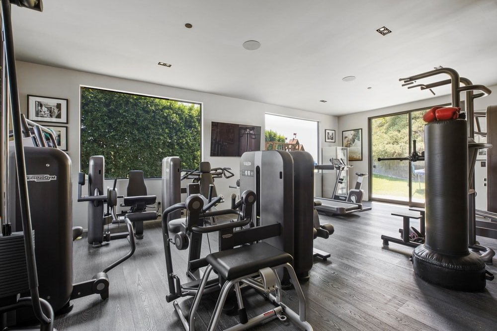 This other angle of the home gym showcases the large glass windows and doors that let in an abundance of natural lighting. Image courtesy of Toptenrealestatedeals.com.