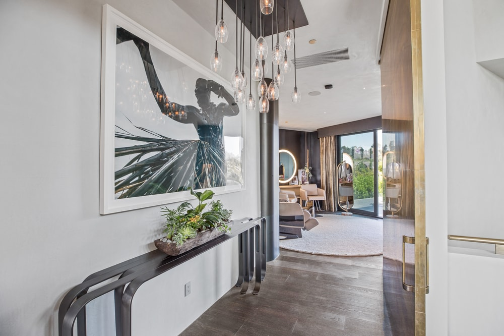 This is the hallway leading to the salon. It has a modern console table and atworks as well as decorative lighting. Image courtesy of Toptenrealestatedeals.com.
