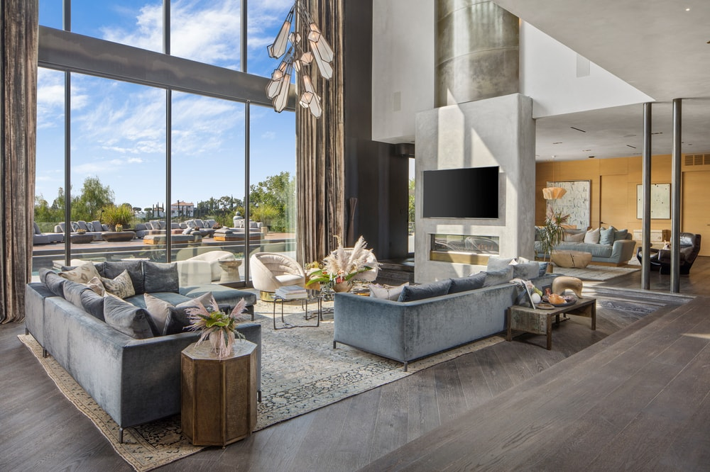 This is the large living room with a tall glass wall on one side, a modern fireplace beneath the wall-mounted TV across from the comfortable sofas. Image courtesy of Toptenrealestatedeals.com.
