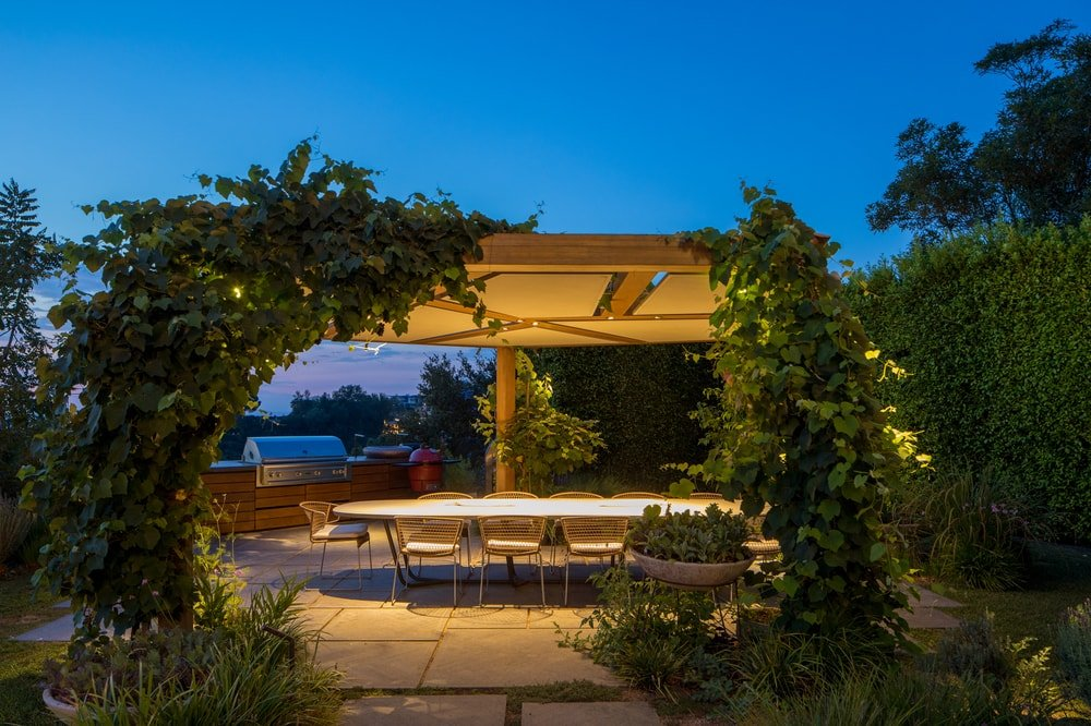 This is a nighttime view of the grapevine pergola showcasing the warm yellow glow of the whole area that makes it stand out. Image courtesy of Toptenrealestatedeals.com.
