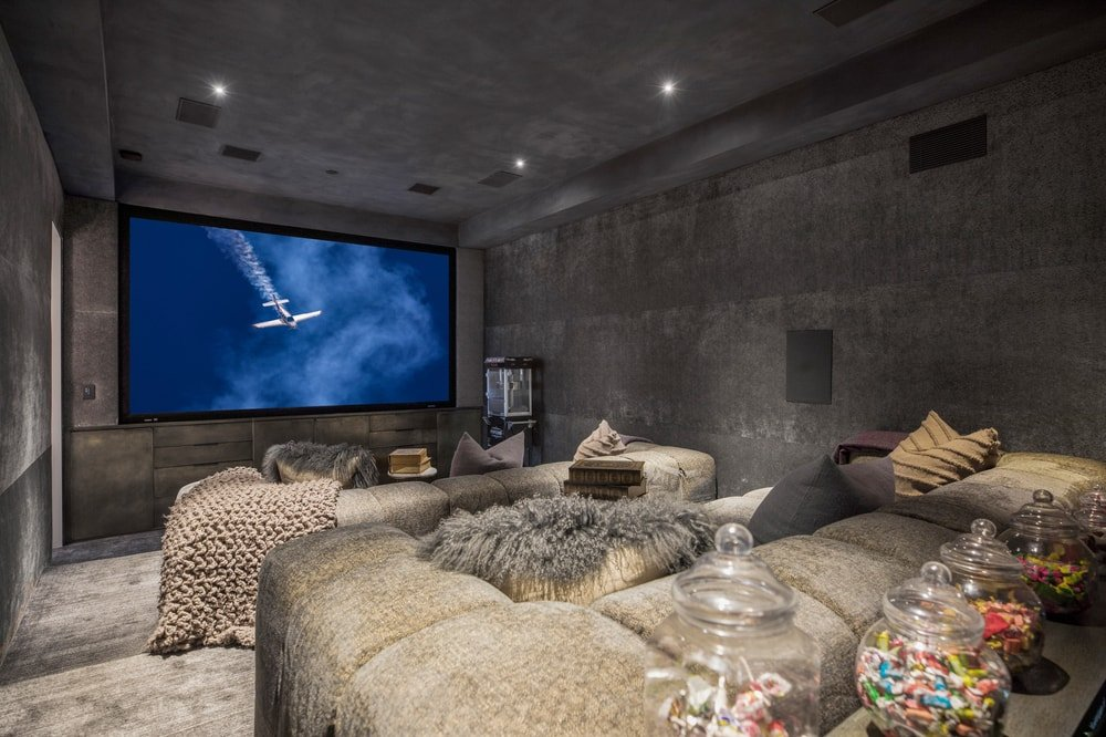 This is the home theater with a large screen at the far end of the room across from the comfortable sofas complemented by gray walls and ceiling. Image courtesy of Toptenrealestatedeals.com.