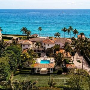 This is an aerial view of the beachfront property with earthy exteriors that go well with the surrounding landscape of green trees, grass, shrubs and the green tennis court. Image courtesy of Toptenrealestatedeals.com.