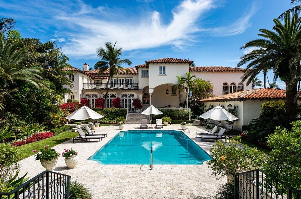 This is the back of the house featuring a large pool that stands out against the beige tone of the house exteriors and walkways. These are then complemented by the surrounding green landscape of tropical trees and shrubs. Image courtesy of Toptenrealestatedeals.com.