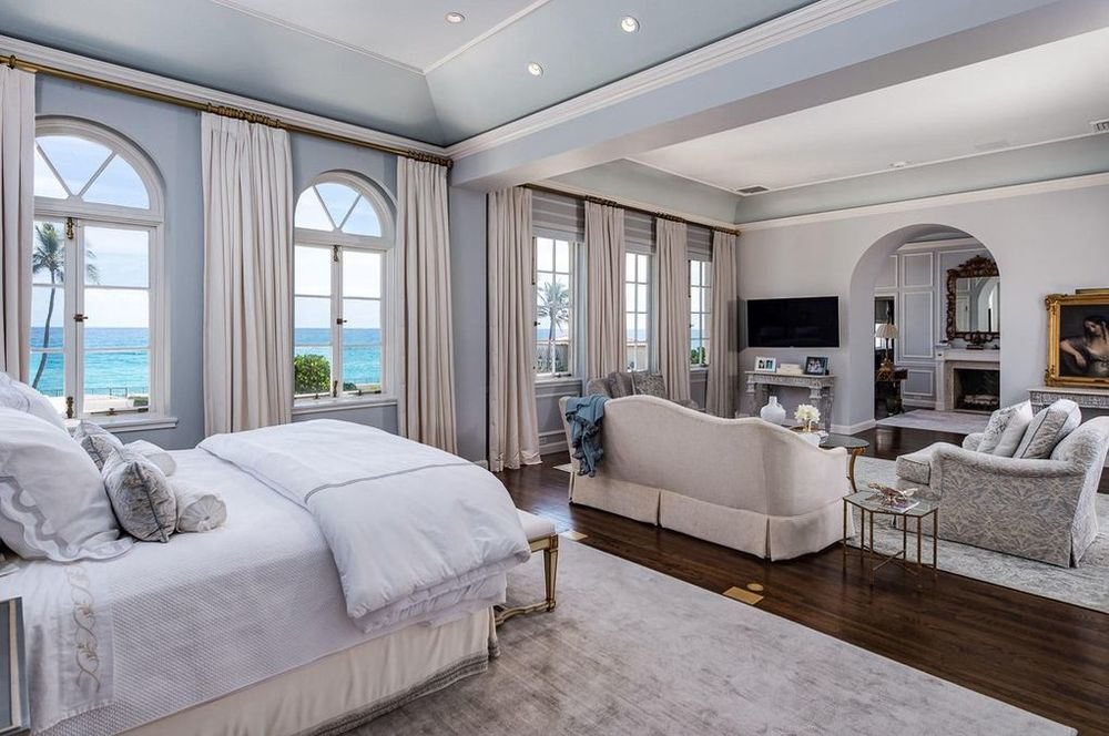The light beige bed matches well with the beige sofa set of the sitting area across from the bed. These are then topped with cove ceilings. Image courtesy of Toptenrealestatedeals.com.