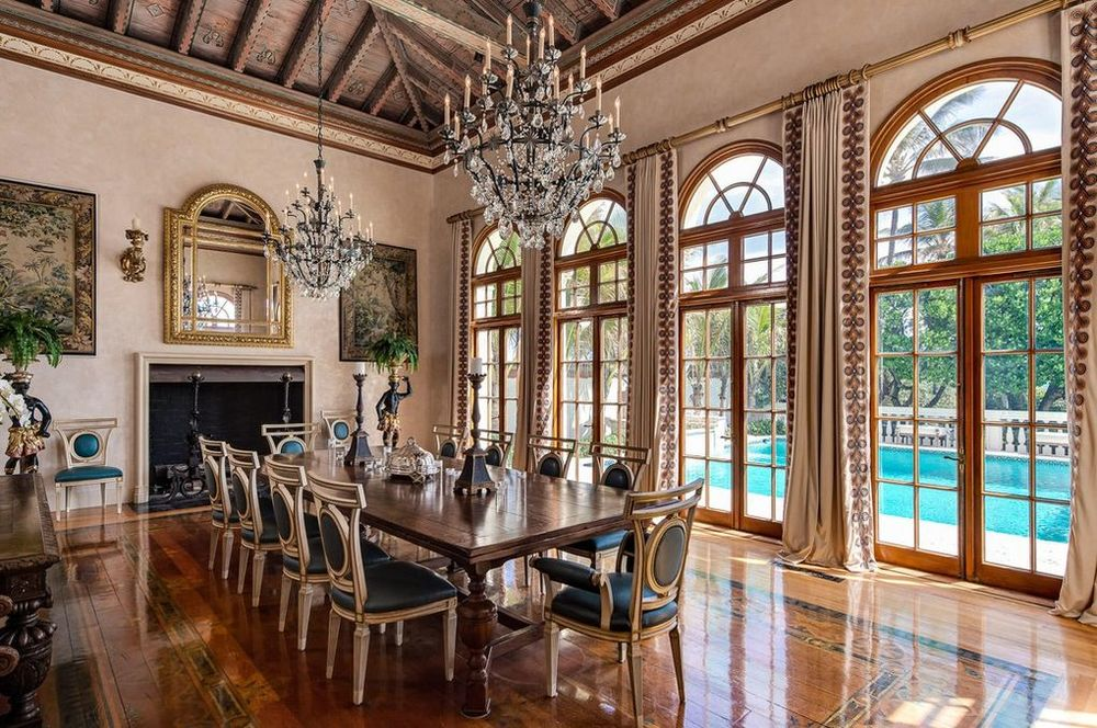 This is the formal dining room with a couple of large crystal chandeliers hanging over the long wooden dining table illuminated by the natural lights of the tall arched windows. Image courtesy of Toptenrealestatedeals.com.