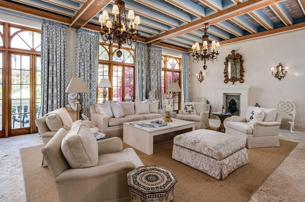 The intricate details of the curtains and the ceiling with chandeliers complement the large beige sofa set of the family room. These are then warmed by the fireplace on the far side. Image courtesy of Toptenrealestatedeals.com.