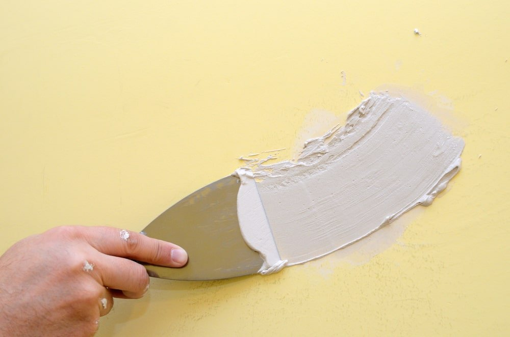 A close look at a hand applying plaster on a wall using a putty knife.