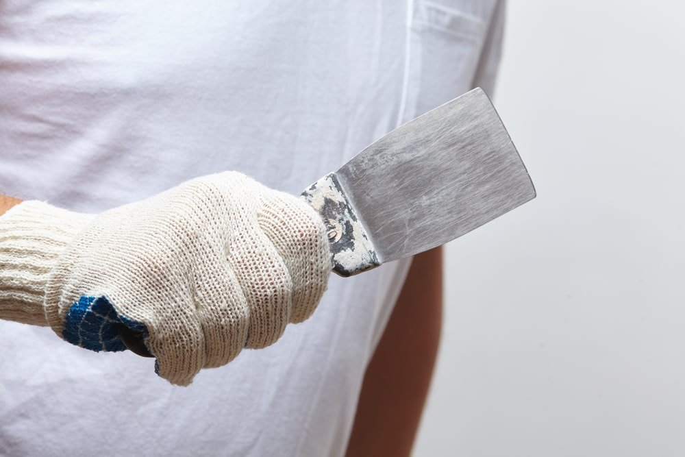 A close look at a gloved worker holding a putty knife.
