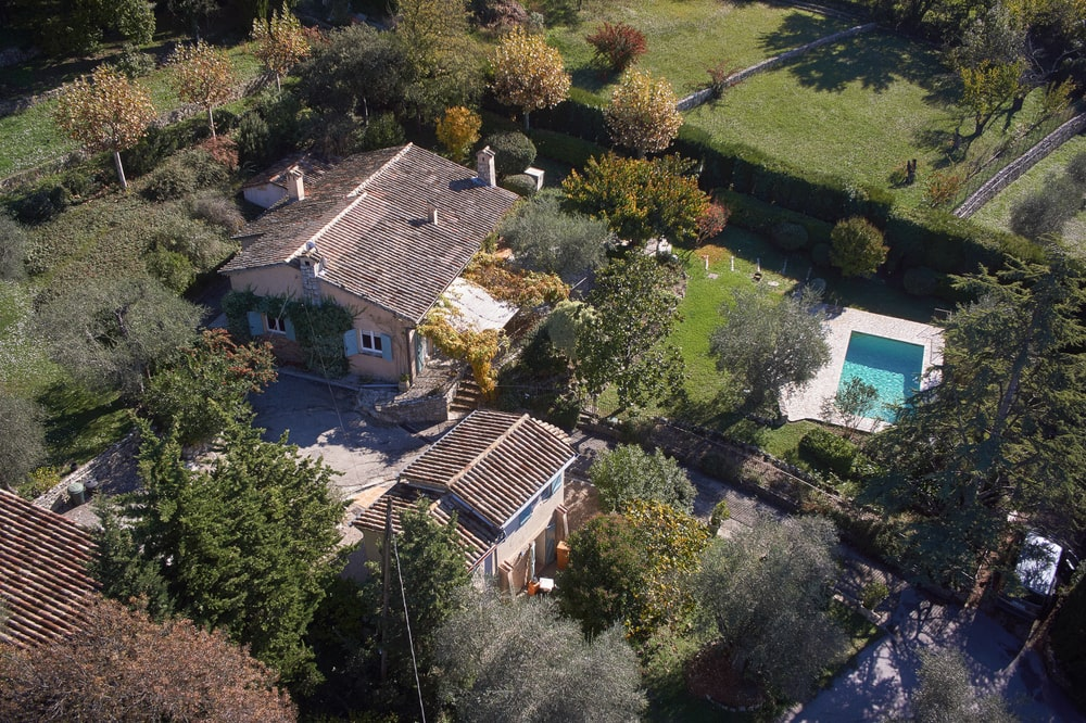 This is an aerial view of the property showing the main house, guest house and pool surrounded by tall trees and shrubs. Image courtesy of Toptenrealestatedeals.com.