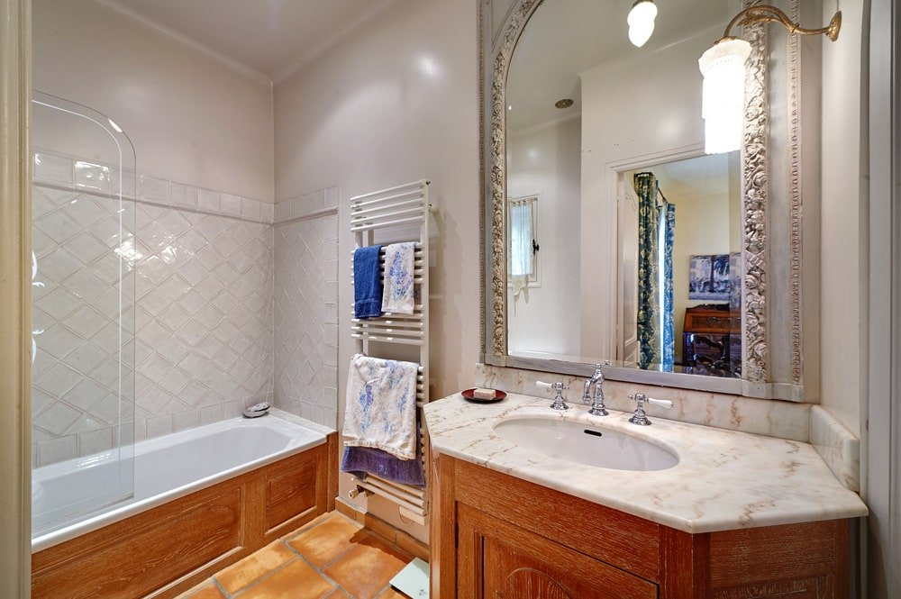 The wooden tone of the bathtub housing matches well with the wooden vanity and the hardwood flooring. These pair well with the beige upper walls. Image courtesy of Toptenrealestatedeals.com.