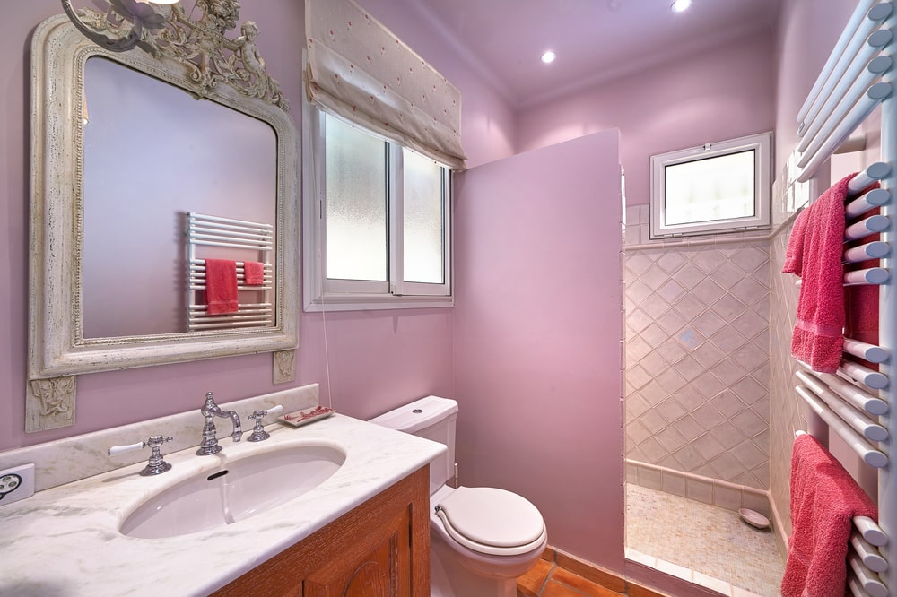The highlight of this bathroom is the pink walls that stand out against white and beige elements. Image courtesy of Toptenrealestatedeals.com.