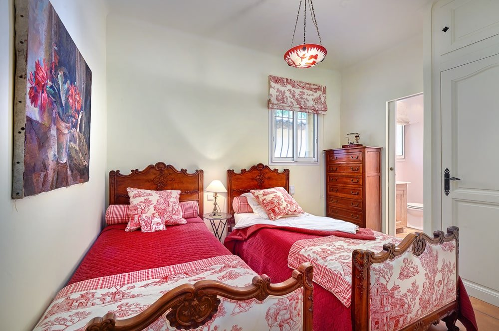 This bedroom also has a couple of red beds that are complemented by the dark brown frame and cabinet dresser at the corner. . Image courtesy of Toptenrealestatedeals.com.
