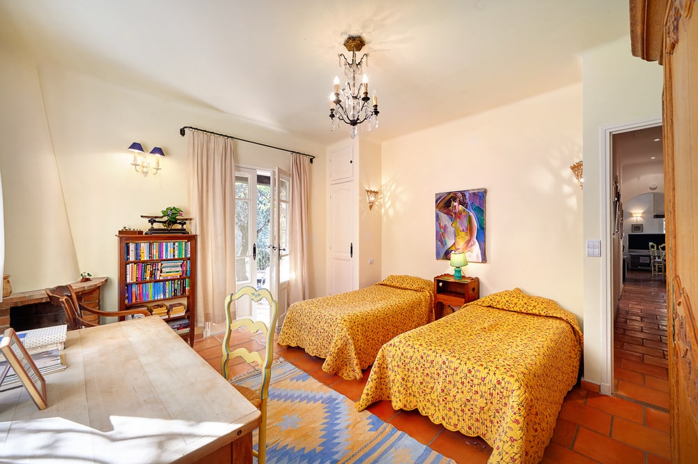 This bedroom has a pair of mustard yellow beds that pair well with the beige wall and ceiling. Image courtesy of Toptenrealestatedeals.com.