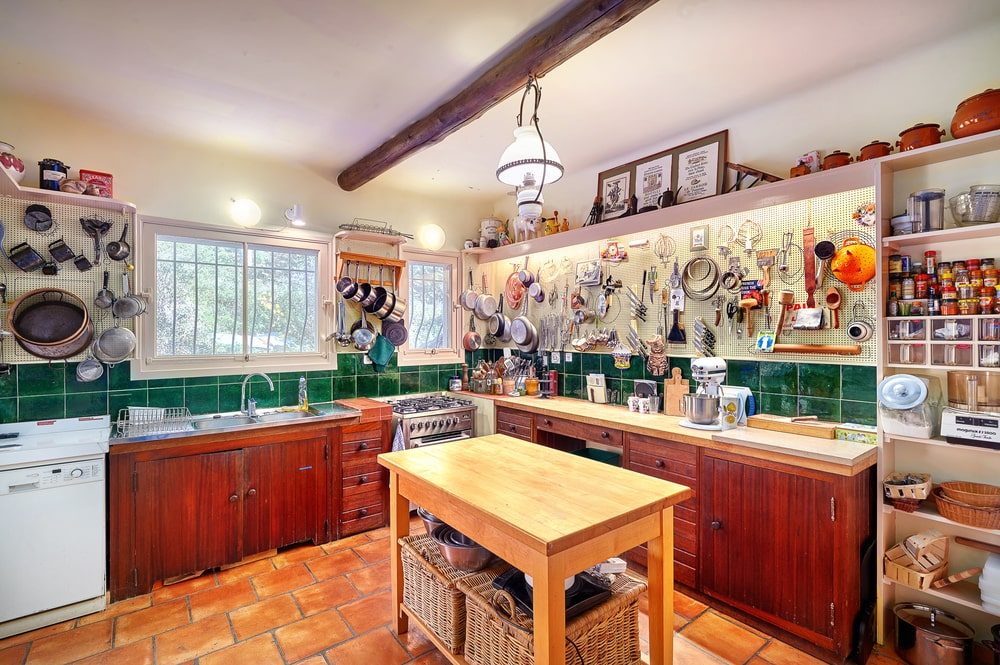 The dark wood cabinetry of the kitchen does not pair well with the wooden kitchen island topped with a pendant light. Image courtesy of Toptenrealestatedeals.com.
