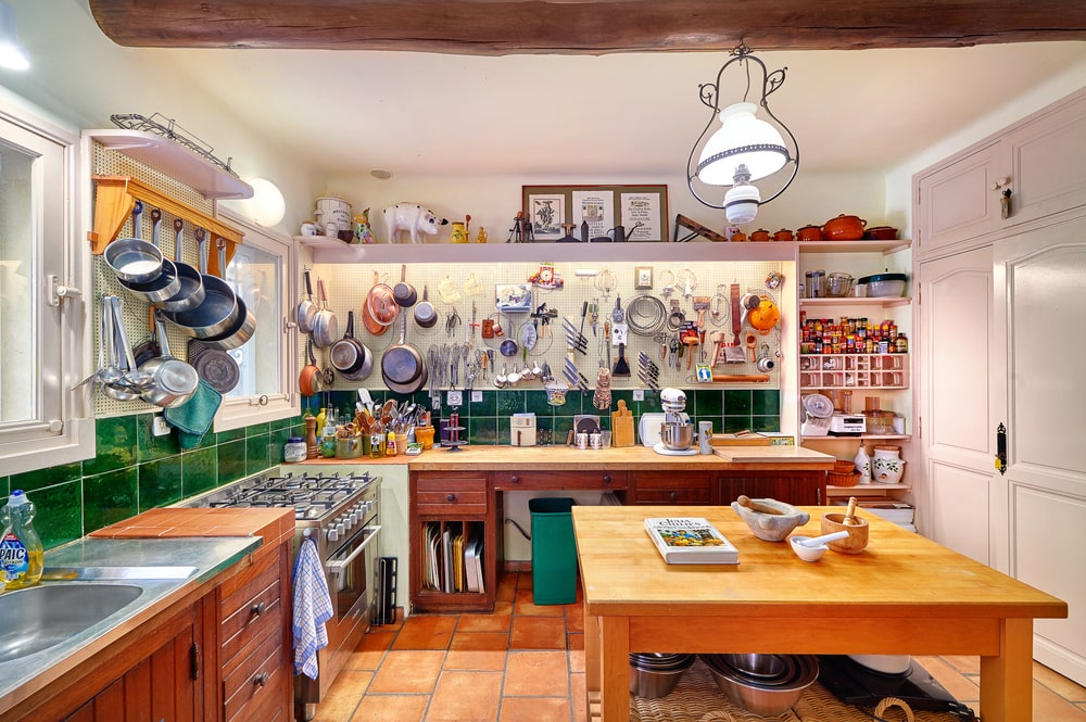 The countertop on the side of the oven has a wide space for a cooking station topped with multiple wall-hanging kitchenware. Image courtesy of Toptenrealestatedeals.com.