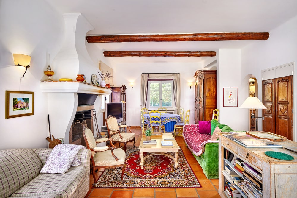 This is the living room with a colorful couch across from the fireplace with a simple white mantle. Image courtesy of Toptenrealestatedeals.com.