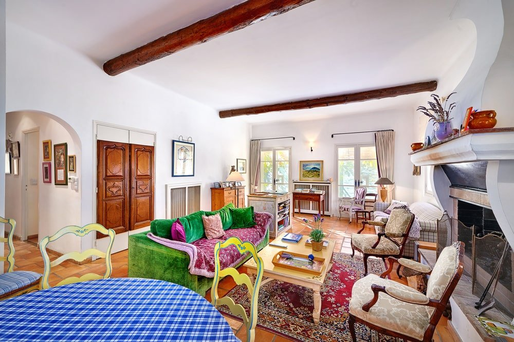 This is a look at the open-plan great room with a dining area, living area and an office at the far end by the two windows. Image courtesy of Toptenrealestatedeals.com.