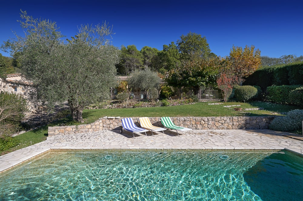 The swimming pool is surrounded by concrete walkways and low stone walls adorned by the lush green landscape and the colorful lawn chairs. Image courtesy of Toptenrealestatedeals.com.