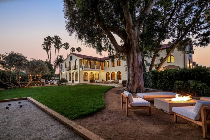 This is a look at the back of the house that has warm beige exterior walls with multiple arches and large windows. These are then complemented by the landscaping that has a large grass lawn and a fire pit under a tall tree. Image courtesy of Toptenrealestatedeals.com.
