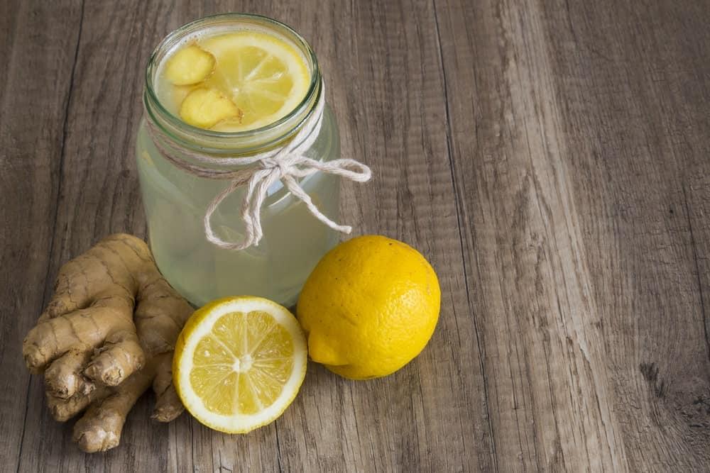 Lemon, ginger, and water detox on wooden background.