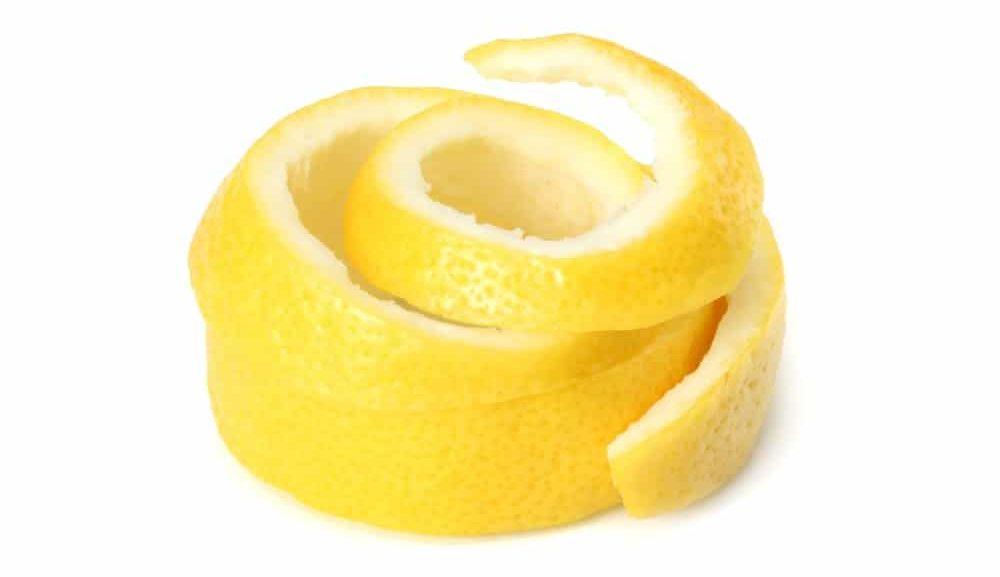 Peeled skin of a lemon against white background.