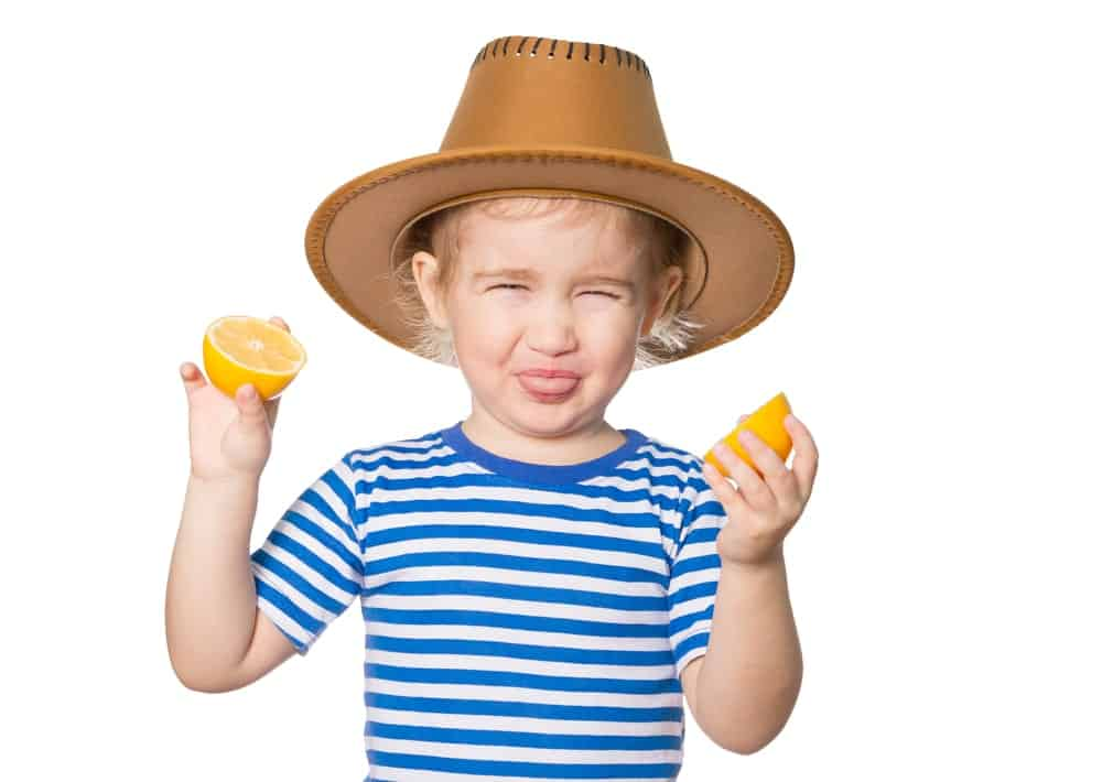 Child with a sour face holding sliced lemons.