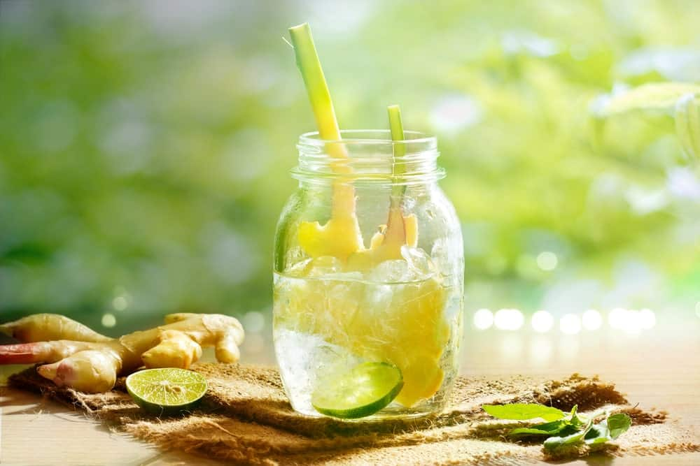Lemon water in a jar with ginger and lime slice on the side.