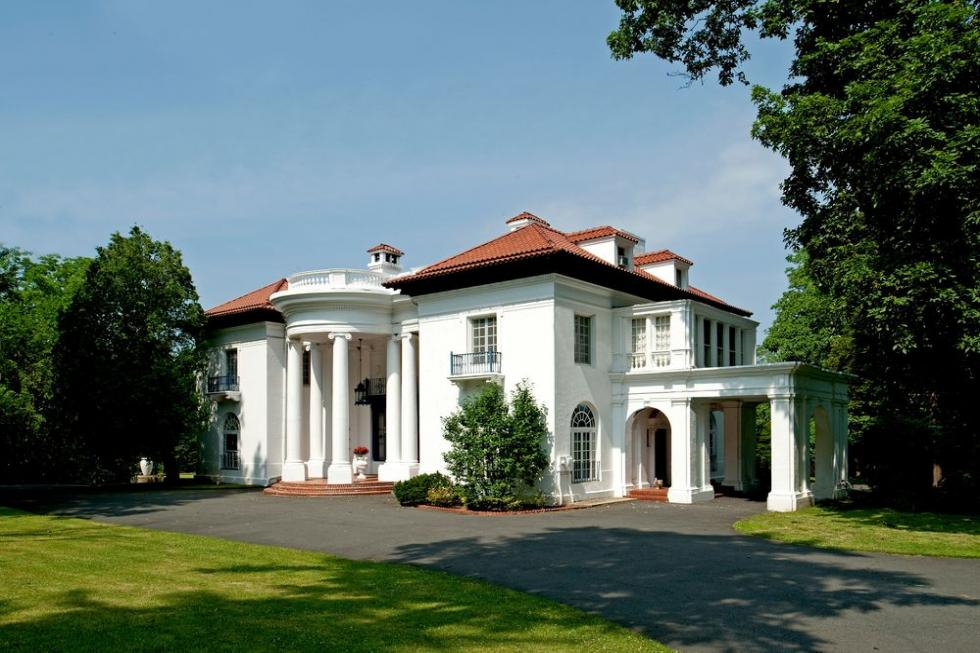 This is a look at the front of the mansion with brilliant white exteriors contrasted by red roofs and an asphalt driveway adorned by lush landscape. Image courtesy of Toptenrealestatedeals.com.