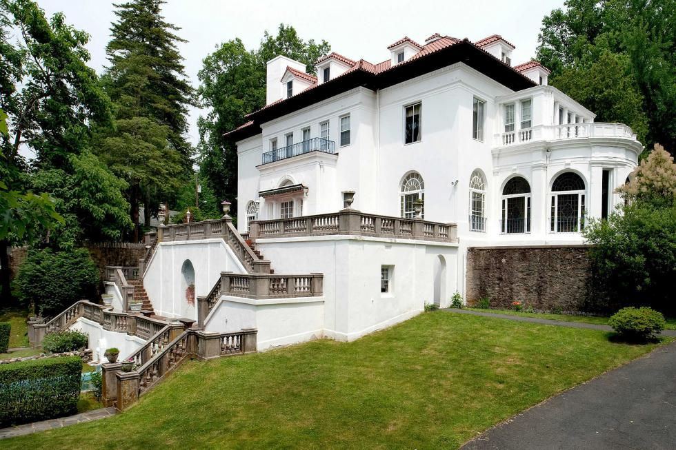 This is a look at the side of the house with lots of windows that complement the bright white walls adorned with tall trees. Image courtesy of Toptenrealestatedeals.com.