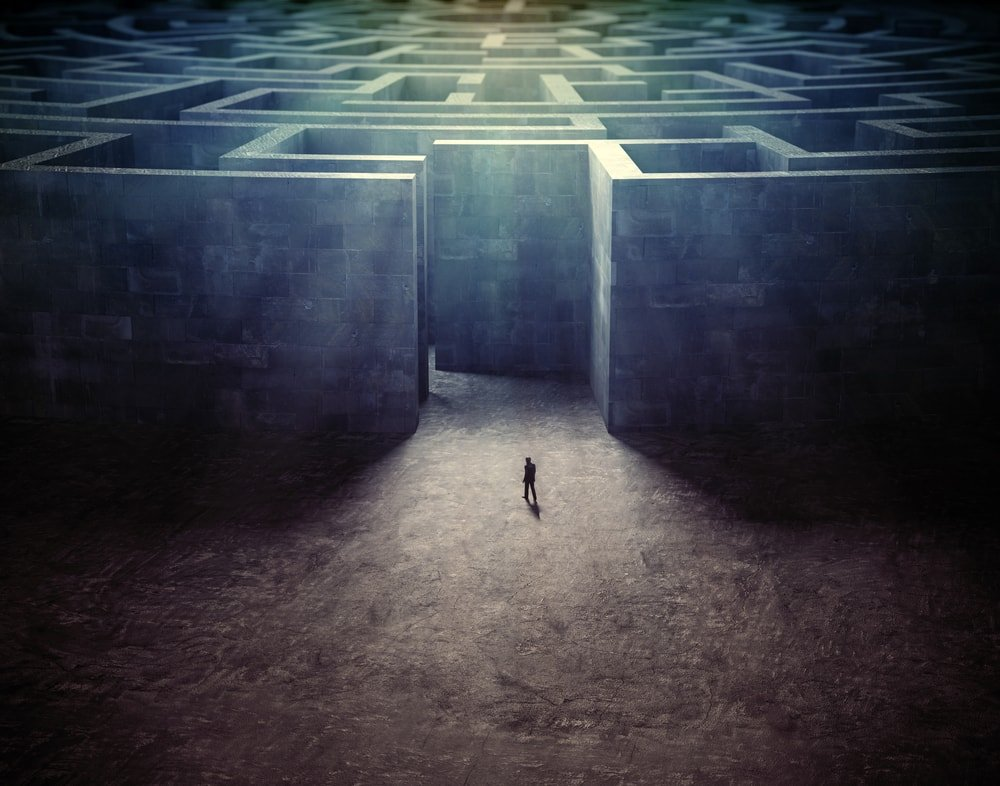 Tiny man entering a huge monolithic labyrinth.
