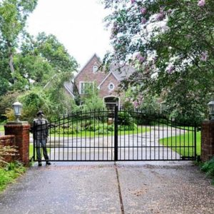 This is a look at the property from the vantage of the wrought-iron gate that is supported by red brick pillars adorned with out lamps. Image courtesy of Toptenrealestatedeals.com.