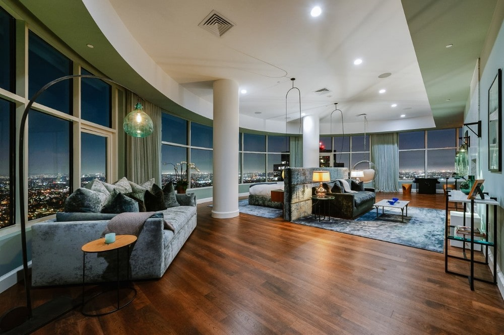This is the primary bedroom with a spacious hardwood flooring, a large curved glass wall that encircles almost the whole room. This room also has large white pillars, sofas and a bed facing the sweeping view of the city. Image courtesy of Toptenrealestatedeals.com.