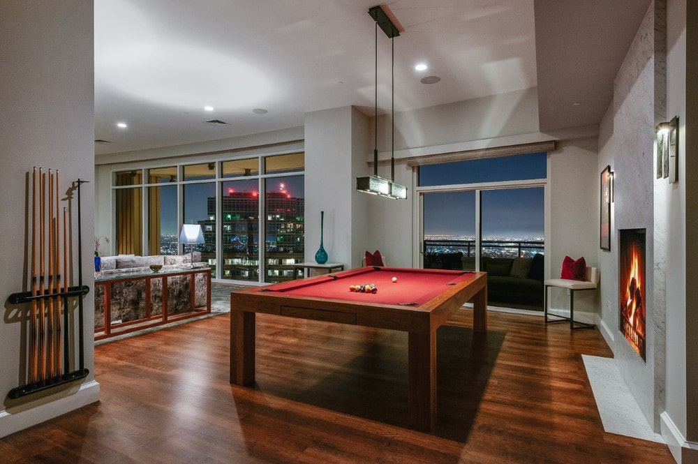 A few steps from the living room is this game area with a alrge pool table that blends well with the hardwood flooring. Image courtesy of Toptenrealestatedeals.com.