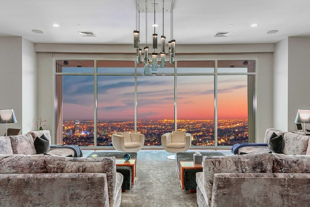 This is the spacious living room that has a couple of large sectional sofas and coffee tables facing the large glass wall on the far side. Image courtesy of Toptenrealestatedeals.com.