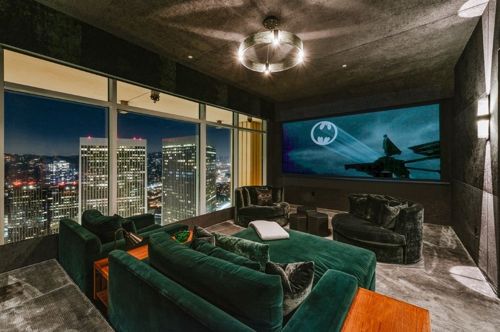 This is the home theater room with a large projected screen on the far end across from the comfortable dark sofas and armchairs. One side has glass walls with view of the city. Image courtesy of Toptenrealestatedeals.com.