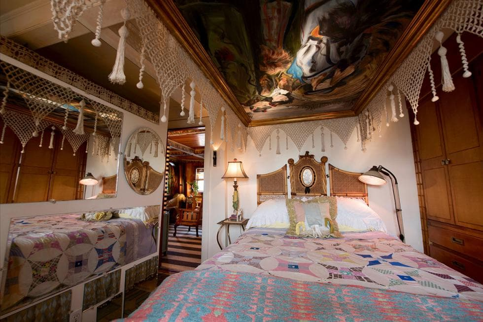 This is the bedroom with a colorful and patterned bed reflected on the large mirror wall on the sie that gives the room an illusion of being bigger than reality. Image courtesy of Toptenrealestatedeals.com.