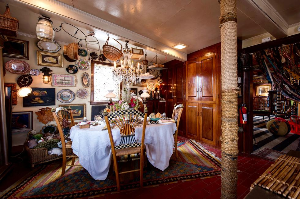 This is the informal dining area with pillars covered in wicker ropes and the walls and ceiling are filled with various rustic decorations. Image courtesy of Toptenrealestatedeals.com.