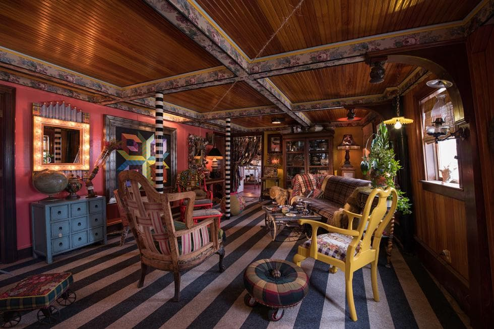 This is the colorful living room with various sofas and armchairs complemented by the different colorful patterns on the pillars, floor and exposed beams of the ceiling. Image courtesy of Toptenrealestatedeals.com.