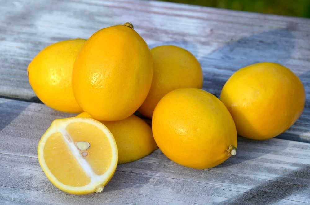 Meyer lemons on a wood plank table.