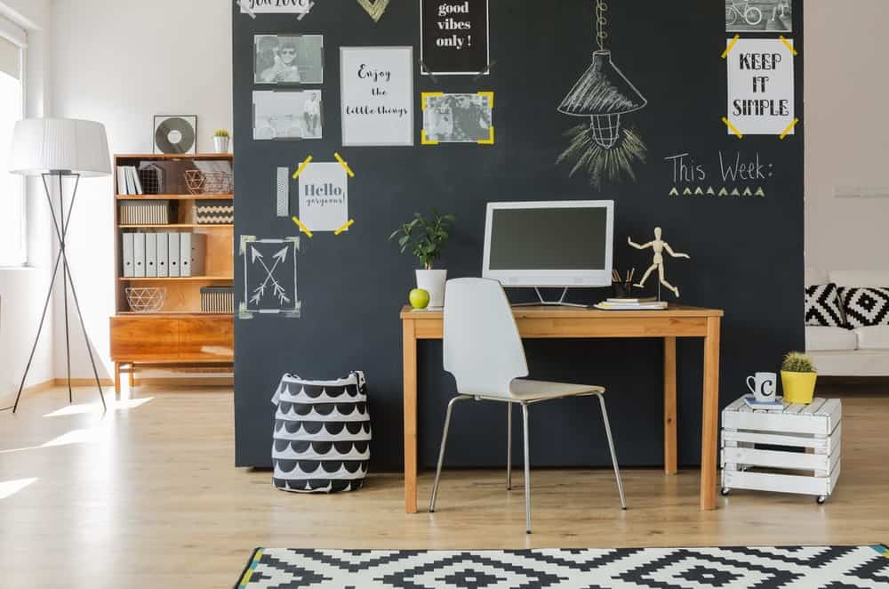 Home office with wooden desk and modern chair against a chalkboard wall.