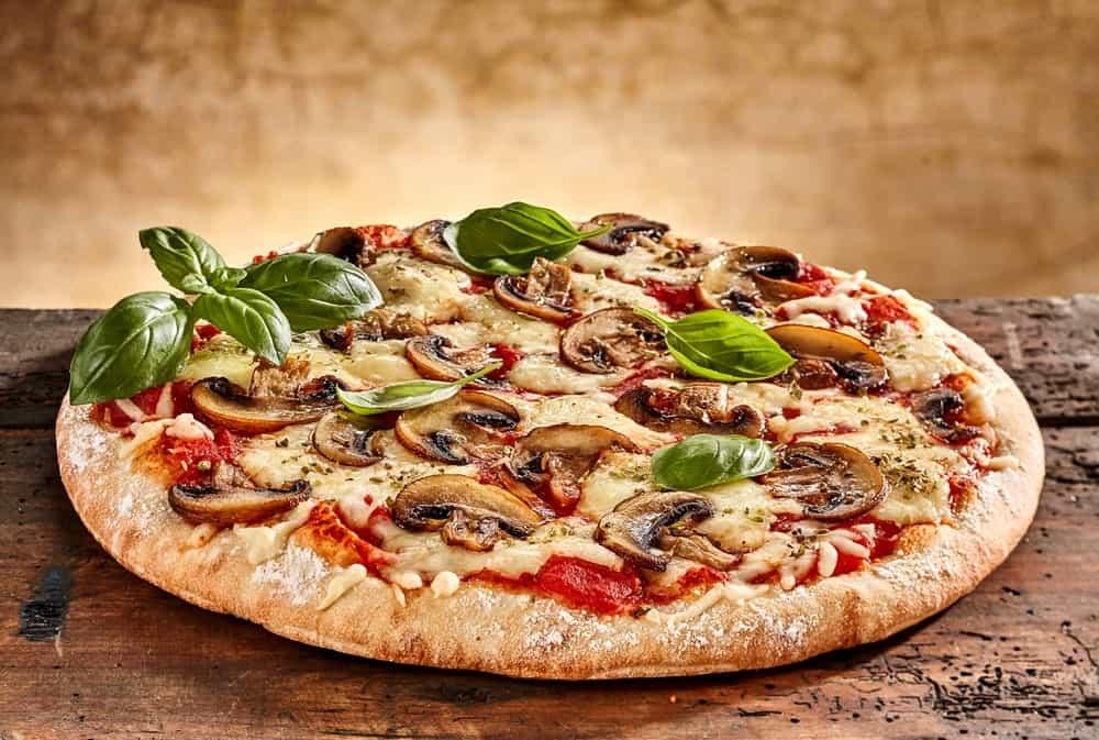 Mushroom pizza on a rustic table.