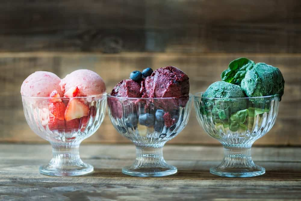Three glasses of nice cream with flavors of banana, raspberry, and spinach on wooden background.