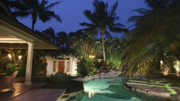 This is a look at the back of the house with a lagoon-style pool surrounded by thick shrubs, tall trees and decorative mosaic stone walkways that are all complemented by the glow of the pool and the outdoor lights. Image courtesy of Toptenrealestatedeals.com.