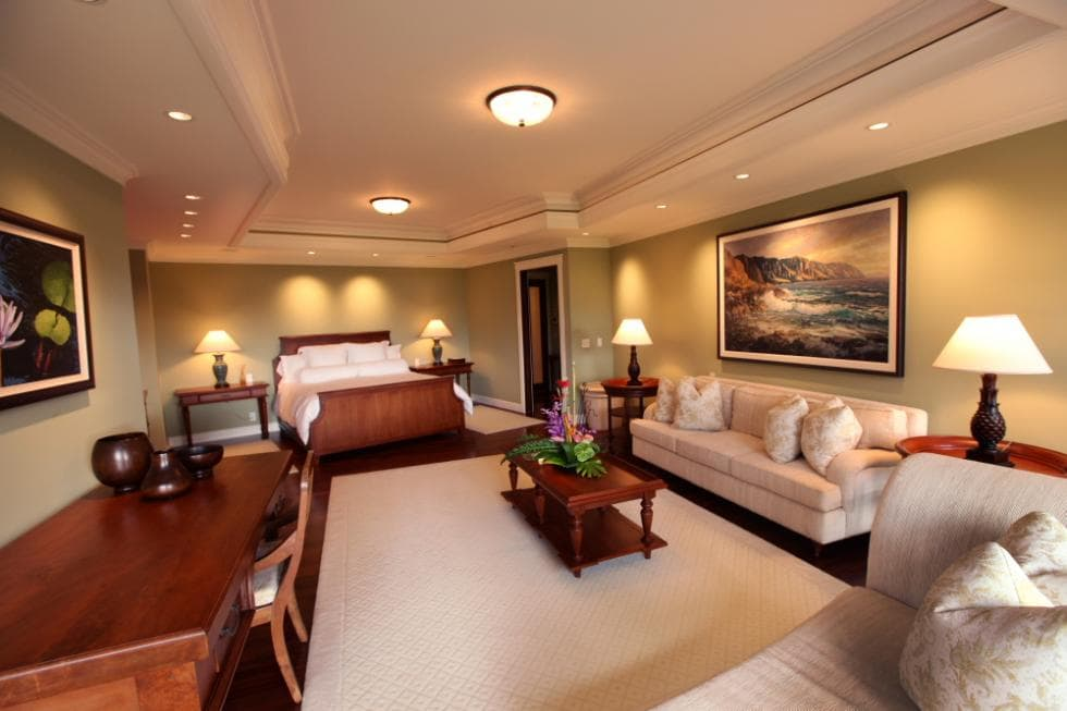 This is the spacious bedroom that has a large wooden sleigh bed on the far side. It has a sitting area with a sofa set at the other side of the room. Image courtesy of Toptenrealestatedeals.com.