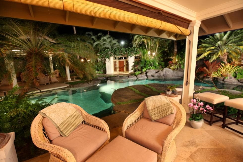 This is the covered patio right beside the lagoon-style swimming pool. This area is fitted with woven wicker armchairs adorned with potted flowers. Image courtesy of Toptenrealestatedeals.com.
