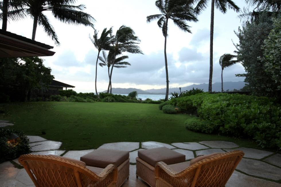 This is the view of the see from the outdoor patio of the house that has a mosaic stone flooring fitted with a couple of woven wicker armchairs. These are complemented by the tall palm trees and a large grass lawn. Image courtesy of Toptenrealestatedeals.com.