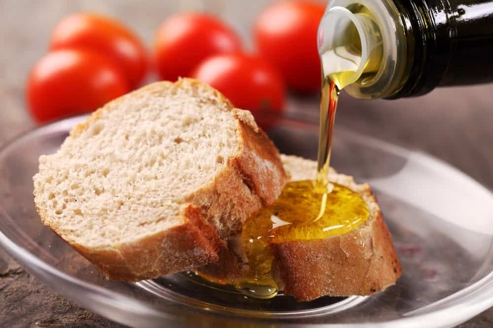 Toasts in a glass plate filled with olive oil.