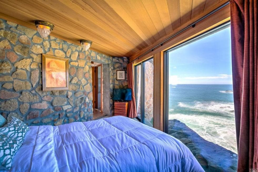 This is the bedroom that has a mosaic stone wall on the side complemented by the wooden ceiling and the frames of the glass wall. Image courtesy of Toptenrealestatedeals.com.